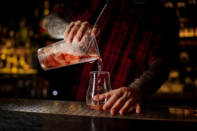 Bartender pouring fresh and tasty cool bittersweet red cocktail into an empty cocktail glass on bar