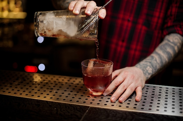 Bartender pouring a red vieux carre cocktail from the measuring cup to a glass on the bar counter