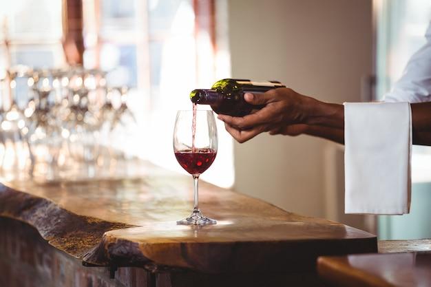 Бармен наливает красное вино в бокал