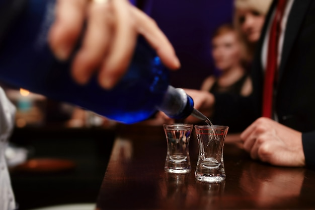 Bartender pouring strong alcoholic drink into small glasses on bar, shots in a nightclub or bar