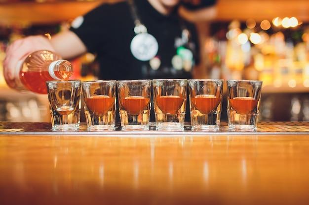 Бармен наливает крепкий алкогольный напиток в небольшие бокалы на баре, снимки.