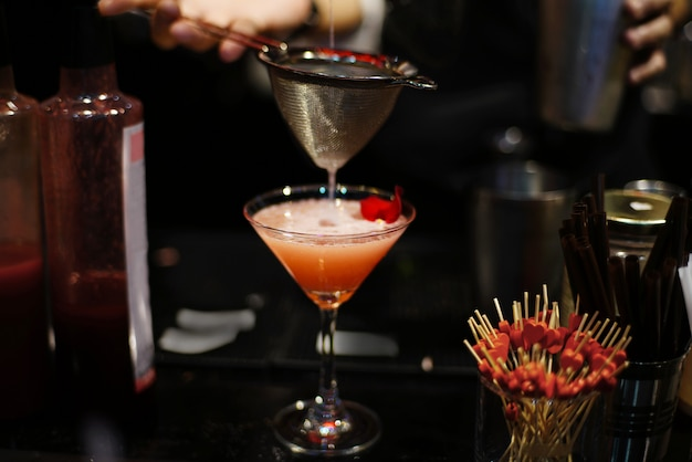 Bartender pouring tasty liquid into orange color cocktail at bar counter in nightclub.