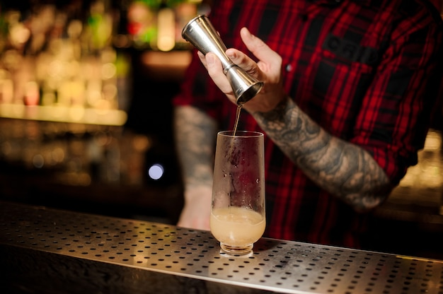 Bartender pouring a trinidad swizzle cocktail from the steel jigger to the glass on the bar counter