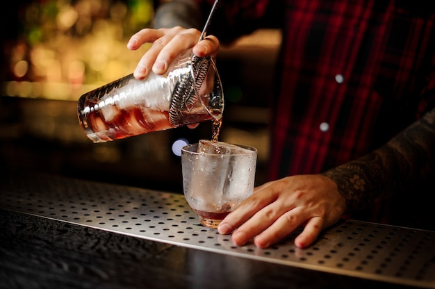 Bartender pouring a vieux carre cocktail from the measuring cup to a glass on the bar counter