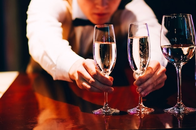 Бармен наливает шампанское. официант наливает шампанское на вечеринку.