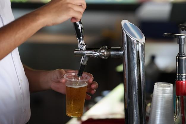 바텐더는 기계에서 유리에 차가운 맥주를 붓습니다