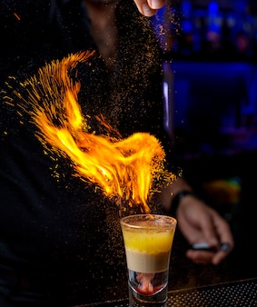 Bartender pours powder into a shot