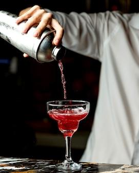 Бармен наливает красный коктейль в бокал с длинным стеблем