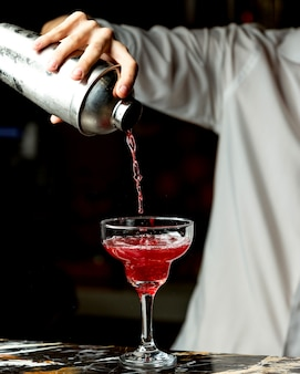 Bartender pours red cocktail into a glass with long stem