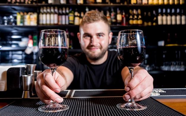 バーテンダーは赤ワインをグラスに注ぎます。ソムリエ。飲食店。ナイトライフ
