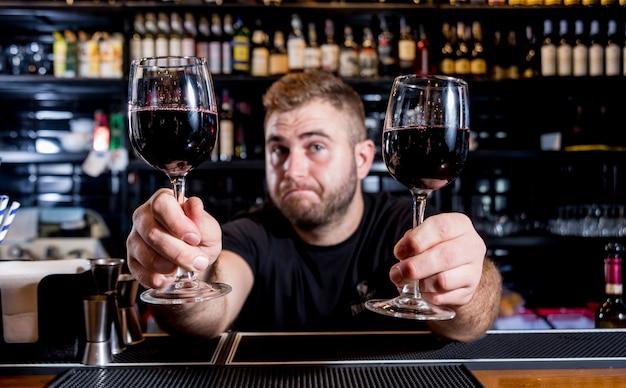 Бармен наливает красное вино в бокал. сомелье. ресторан. ночная жизнь