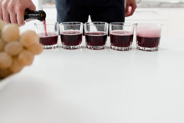 Bartender pours red wine into glasses on white table. red homemade wine in glasses.
