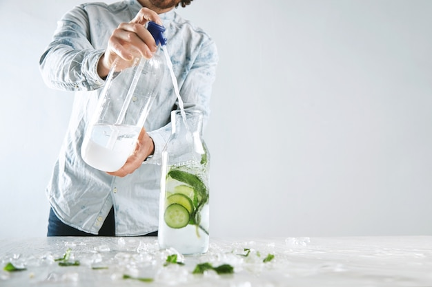 Bartender pours sparkling water in vintage bottle with ice, cucumber and mint from siphone to make cold summer healthy beverage like mojito without alcohol