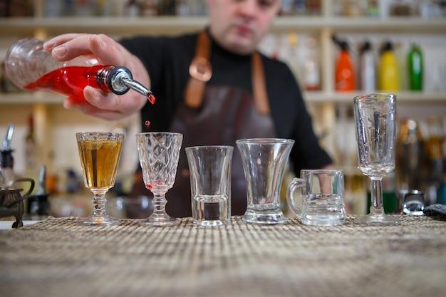 바텐더는 다양한 알코올 음료를 바의 작은 잔에 붓습니다.