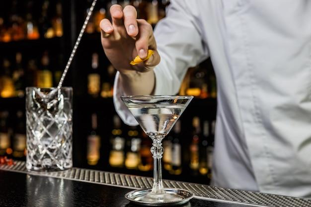 Бармен готовит коктейль в баре, сжимая лимонную цедру над напитком в бокале для мартини