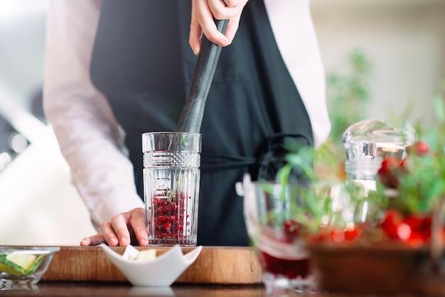 バーテンダーはレストランのテラスでベリーカクテルを準備します