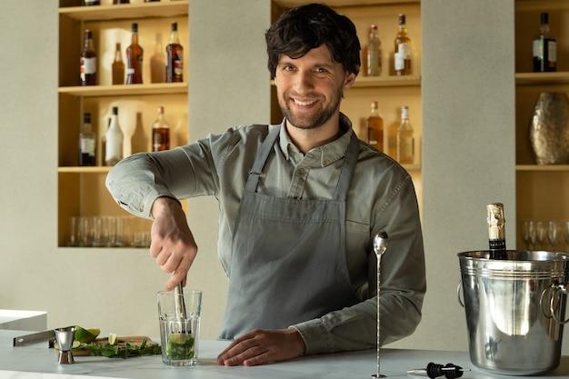Бармен готовит коктейль мохито из мэдлера. бармен измельчает мяту и лайм с мэдлером.