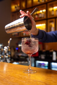 Bartender prepares a cocktail with berries at the bar.