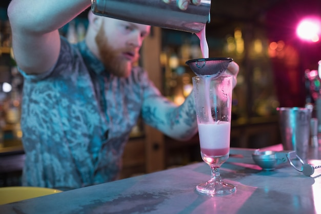 Бармен готовит коктейль у стойки