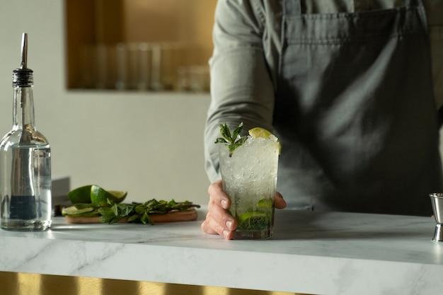 Бармен готовит и смешивает коктейли за барной стойкой, коктейль мохито подается в баре ресторана