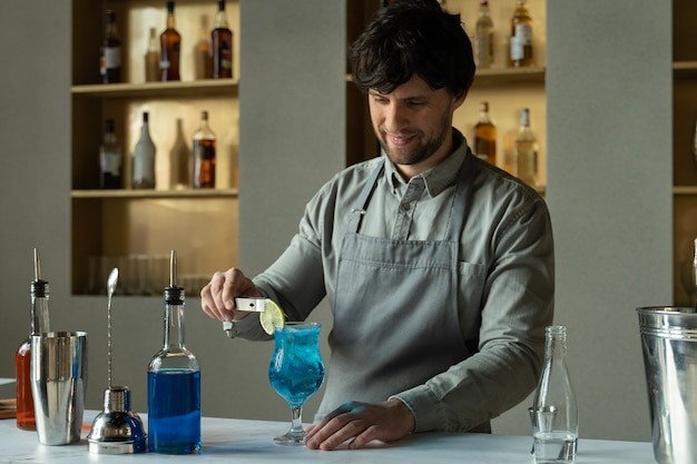 Bartender preparing at the bar counter blue lagoon cocktail man decorates a cocktail with lime