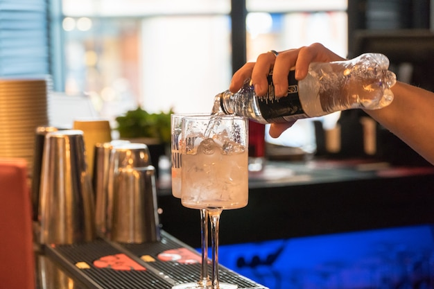 Bartender preparing a cocktail with ice, close-up