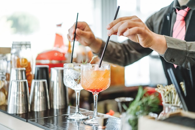 Bartender preparing different cocktails mixing with straws inside bar