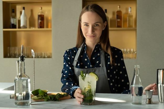 Бармен готовит коктейль мохито в баре ресторана