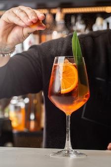 カウンターで準備するバーテンダーaperolspritzクラシックでさわやかなイタリアの食前酒がミキシングされました