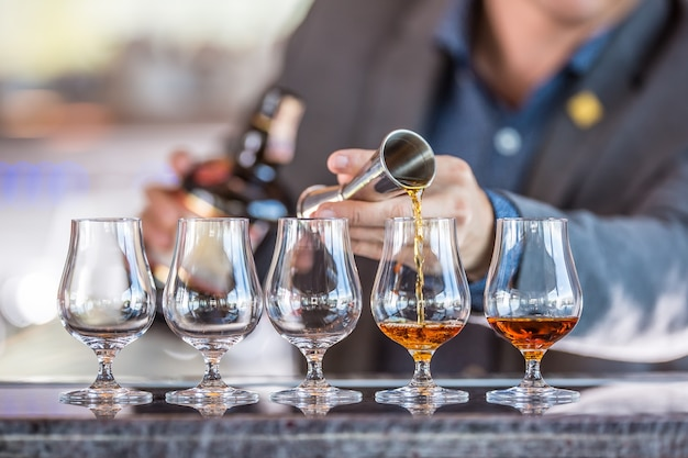 Bartender professional preparing five alcololic drinks he pouring a very high quality rum or cognac