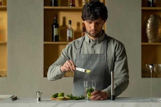 Бармен кладет листья лайма и мяты в стакан, чтобы приготовить коктейль мохито