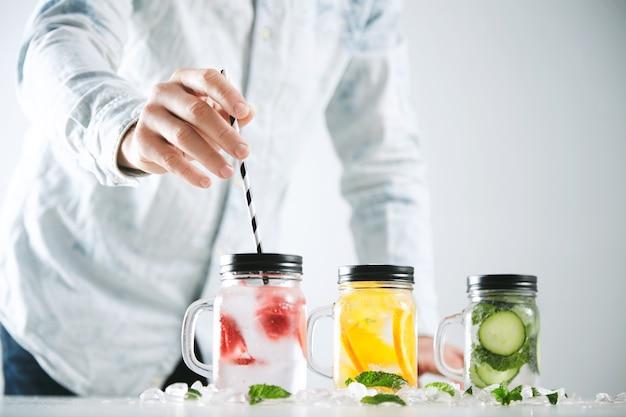 Il barista mette la cannuccia a strisce in un barattolo con limonata fresca fatta in casa fredda a base di ghiaccio, fragola, arancia, cetriolo e menta.