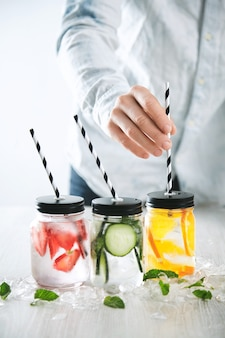 Bartender puts striped drinking straws in jars with fresh cold homemade lemonades made from ice, strawberry, orange, cucumber and mint.