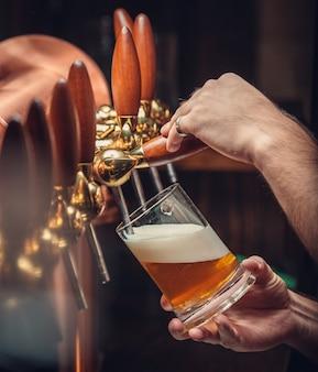 Бармен положить пиво в стакан.