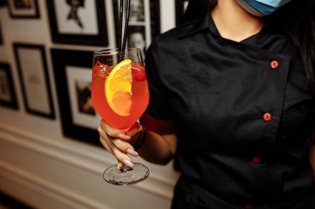 Рука бармена, держащая стакан с напитком aperol spritz