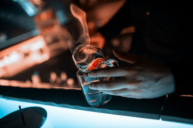 Bartender's hands, glass goblet on the bar counter