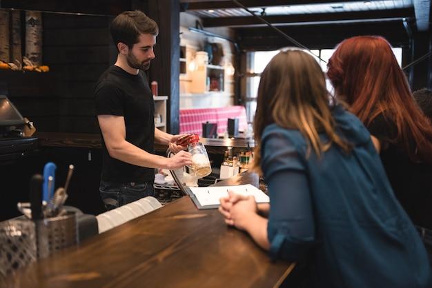 バーカウンターでビールを提供するバーテンダー