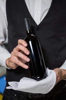 バーカウンターでワインのバーテンダーサービングボトル