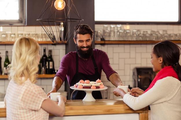 顧客にコーヒーを提供するバーテンダー
