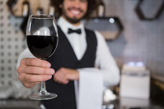 バーカウンターで赤ワインのグラスを提供するバーテンダー