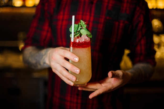Bartender serving a trinidad swizzle cocktail in the glass with tubule and mint leaves on the bar counter