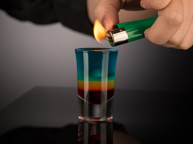 Bartender sets fire to a mixed alcoholic cocktail in a shot glass, close-up
