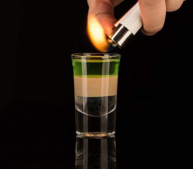バーテンダーがショットグラスのミックスアルコールカクテルに火をつける、クローズアップ