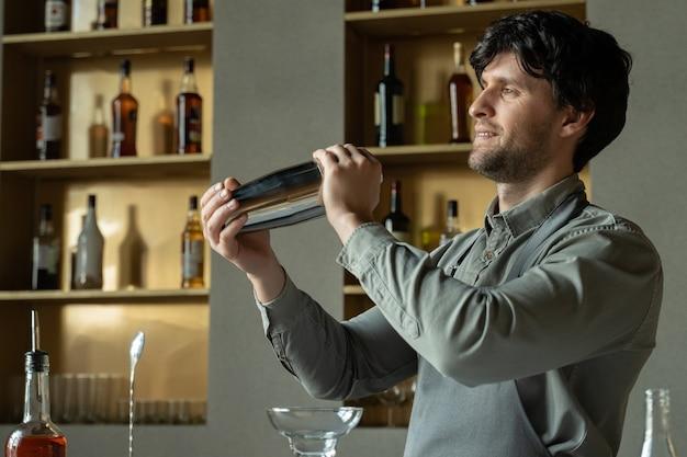 Bartender shaking cocktail shaker in cocktail bar
