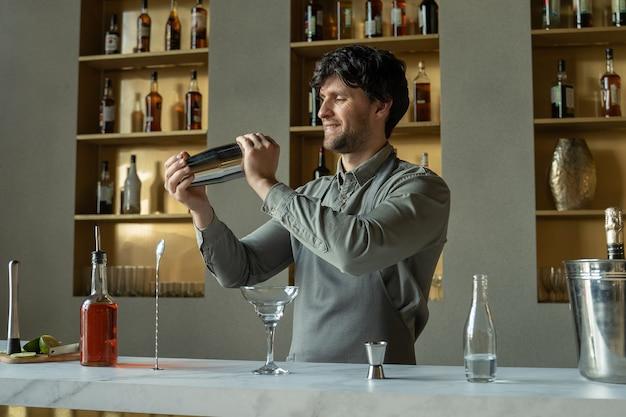 Бармен встряхивает шейкер в коктейль-баре