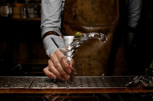 Бармен встряхивая бокал с мартини на прилавке