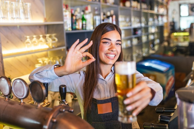 Bartender showing ok sign serving a draft beer at the bar counter