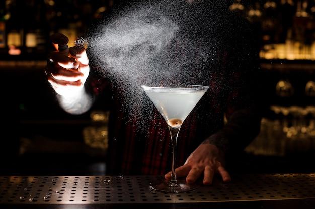 Бармен разбрызгивает горький бокал на элегантный стакан свежего коктейля