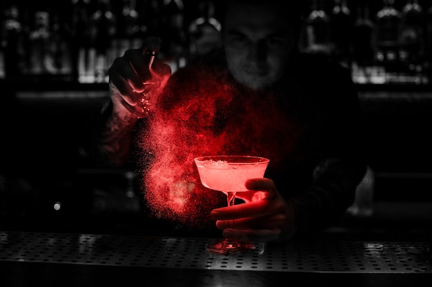 Bartender spraying on the delicious cocktail from the special vaporizer on the bar counter