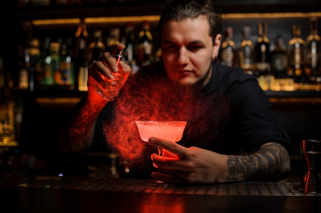 Bartender spraying on the delicious cocktail from the special vaporizer in the red light on the bar counter